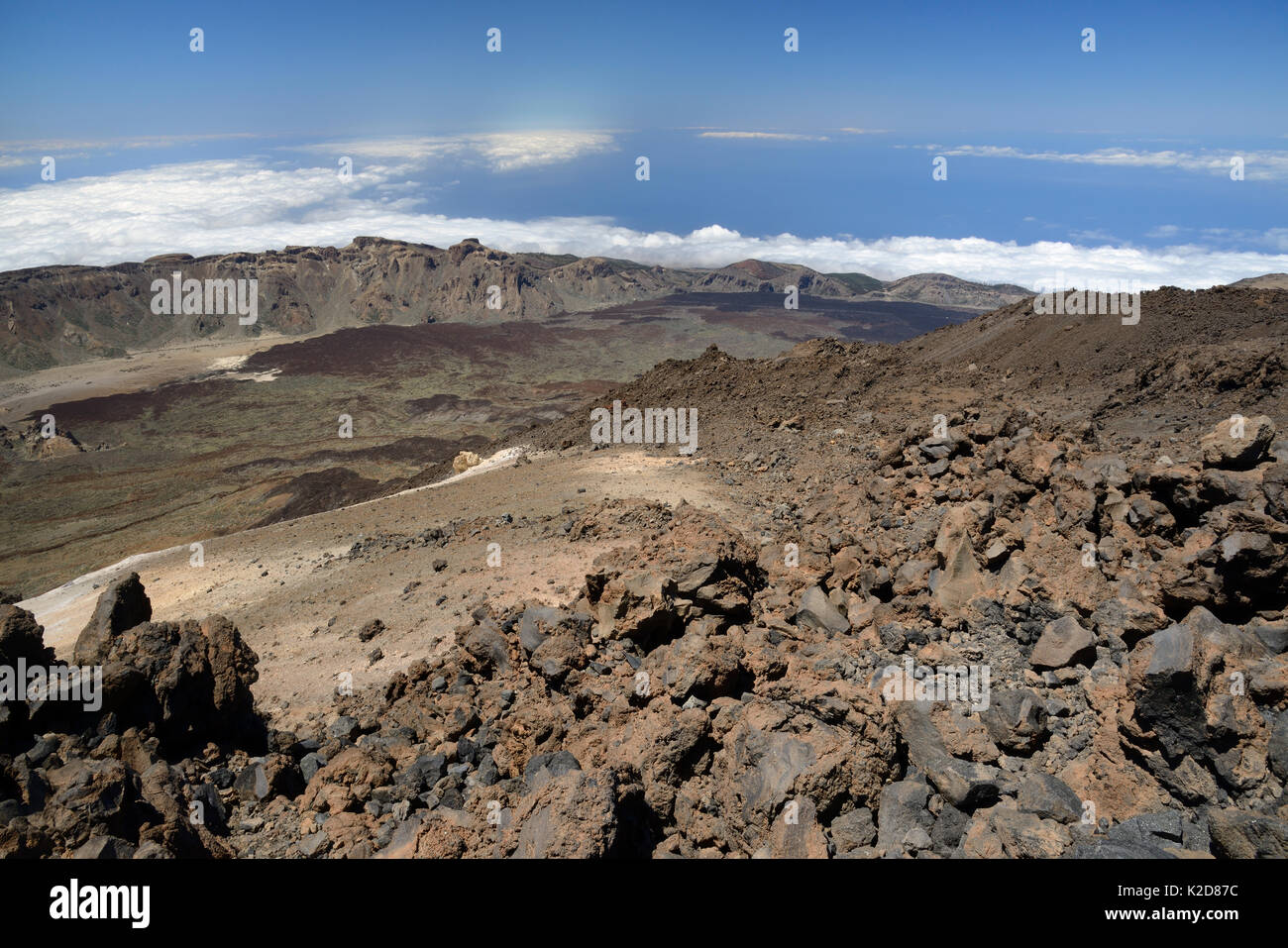 Overview of Las Canadas caldera from the 3700m summit of Mount Teide, the highest mountain in Europe, with old lava flows and pumice deposits, with clouds over the sea in the background, Tenerife, May. - Stock Image