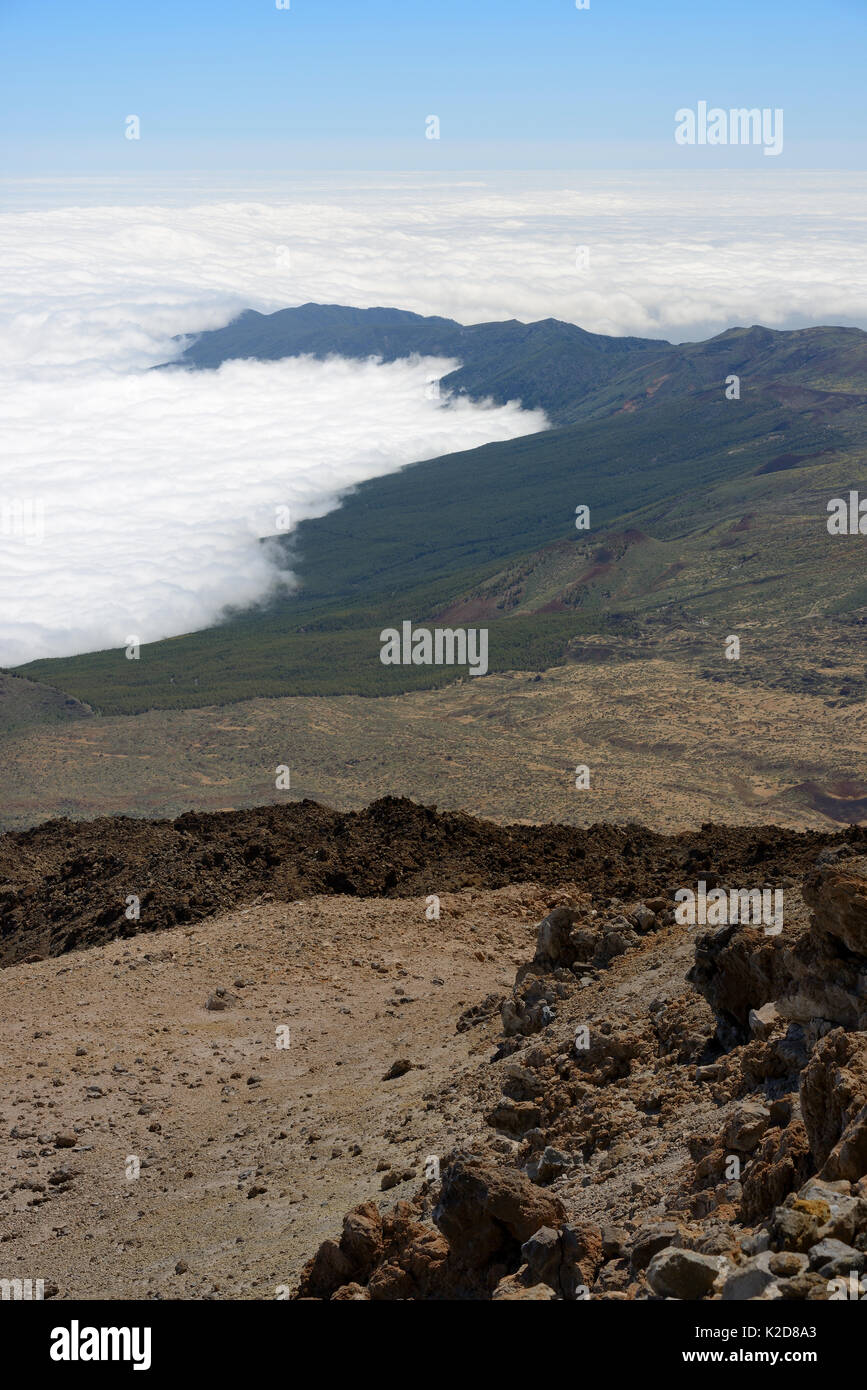 Clouds around the volcanic highlands of Tenerife, viewed from the 3718m summit of Mount Teide, with old lava flows and pumice deposits in the foreground, Tenerife, May 2014. - Stock Image