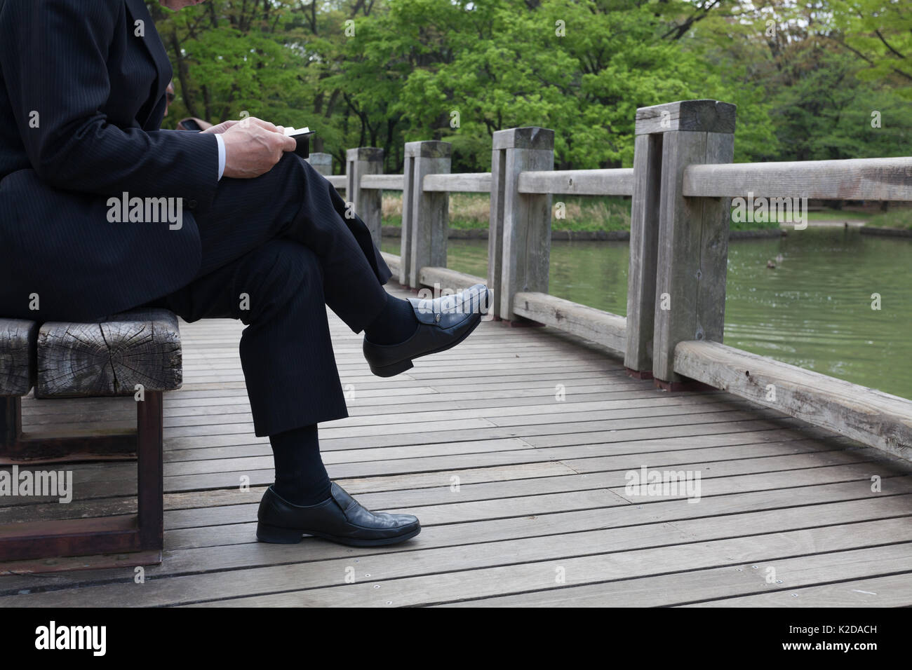 A man in a suit sits crossed legged on a bench in a  park to read a book.  read a book. Yoyogi Park, Tokyo, Japan. Friday April 28th 2017 - Stock Image