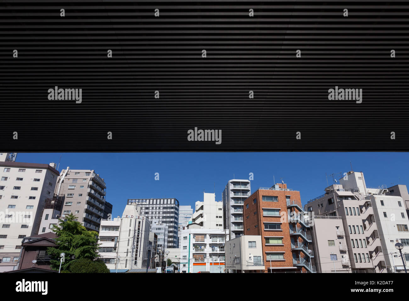 An overpass on the Shuto Expressway closes pout the sky above a view of apartment buildings near Asakusa ,Tokyo, Japan. Friday July 14th 2017 - Stock Image