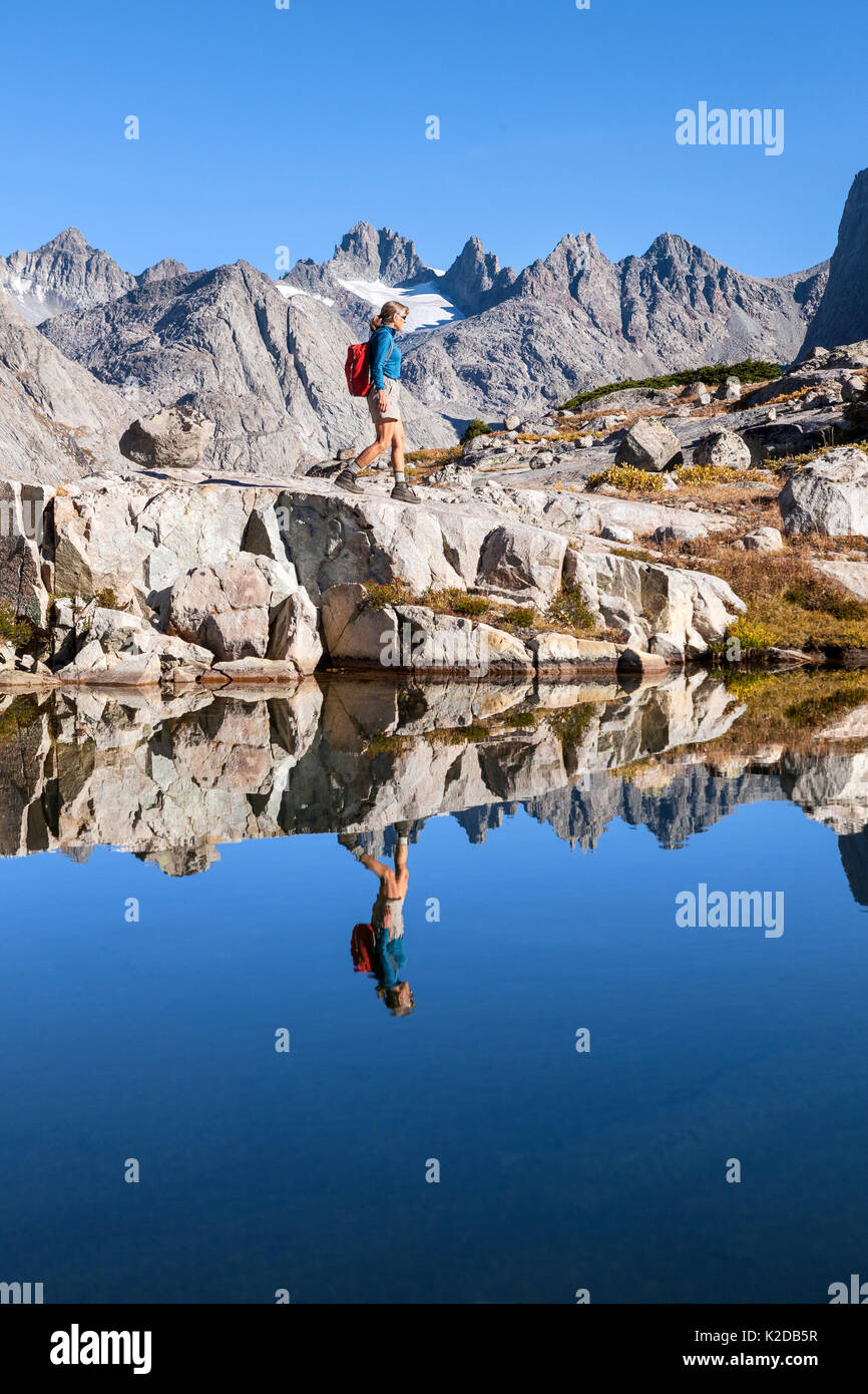 Hiker exploring mountain lake in the  Titcomb Basin, Wind River Range, Bridger Wilderness, Bridger National Forest, Wyoming, USA. September 2015. Model released. - Stock Image