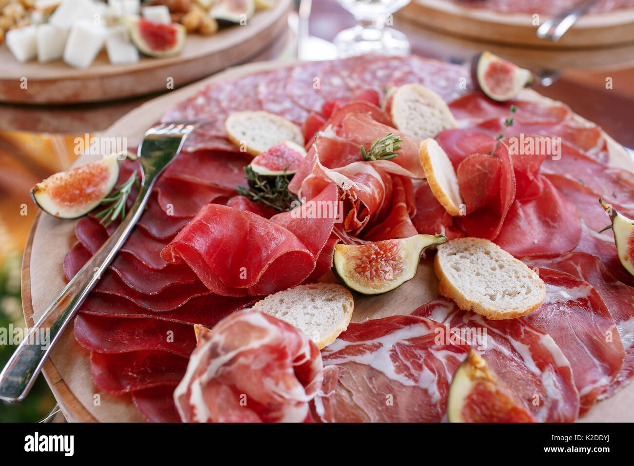 Italian antipasti and appetizers. board with slices prosciutto, salami, dried pork, salami ham with herbs. - Stock Image