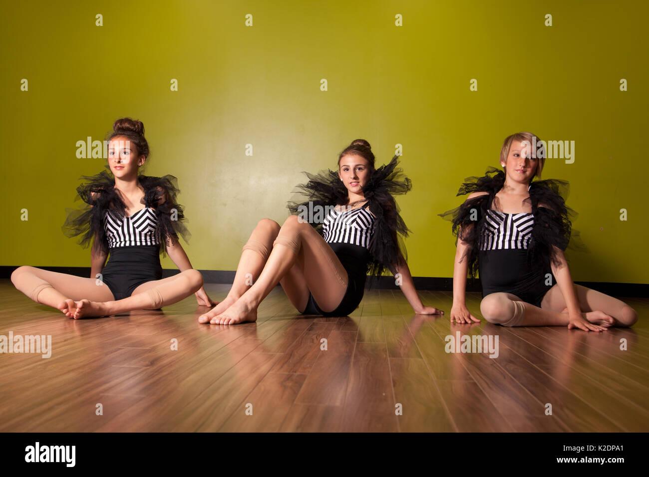 Three teenage models and dancers in costumes pose in studio