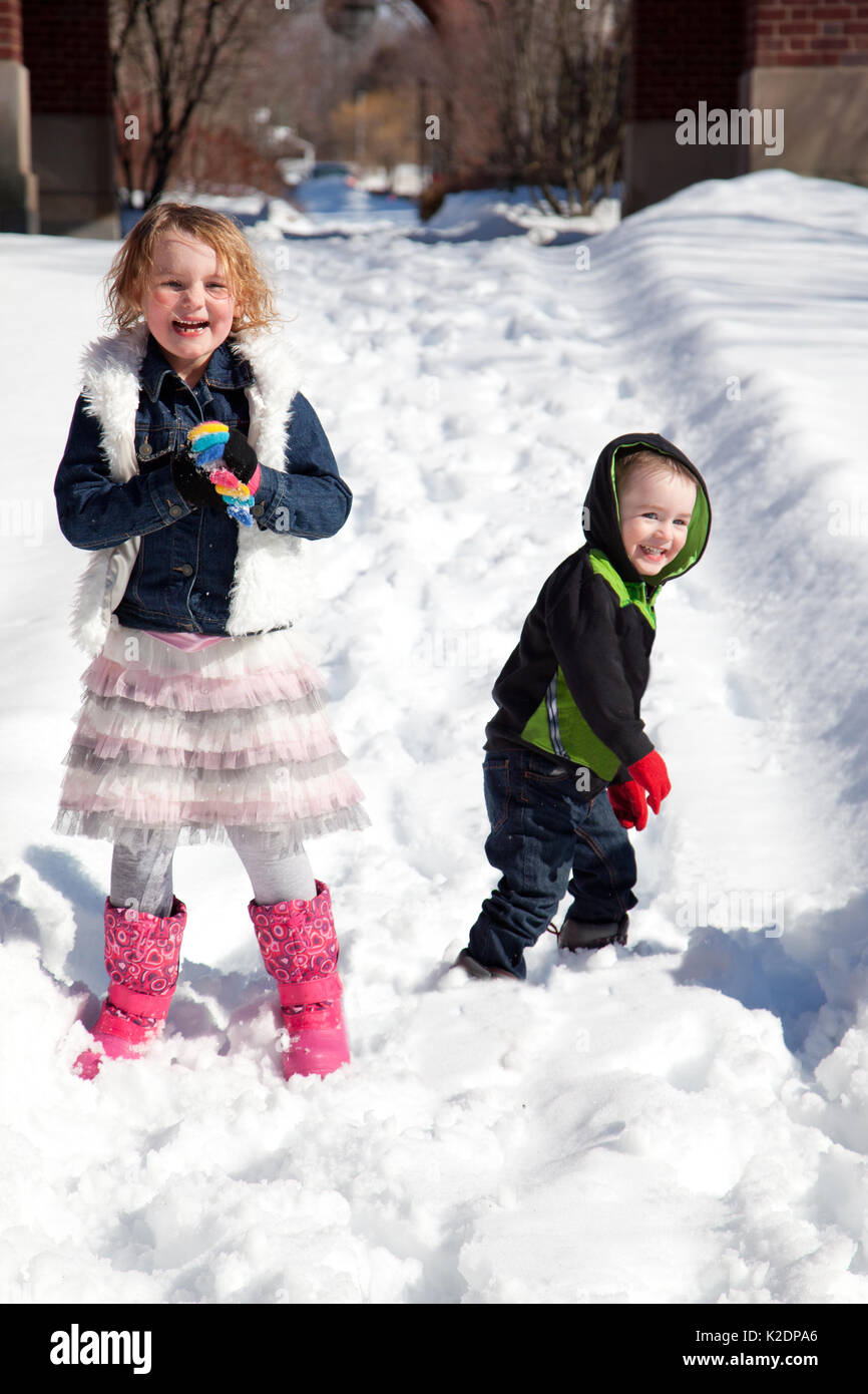 young boy and girl grin and laugh as they have a snowball fight outside in the winter - Stock Image