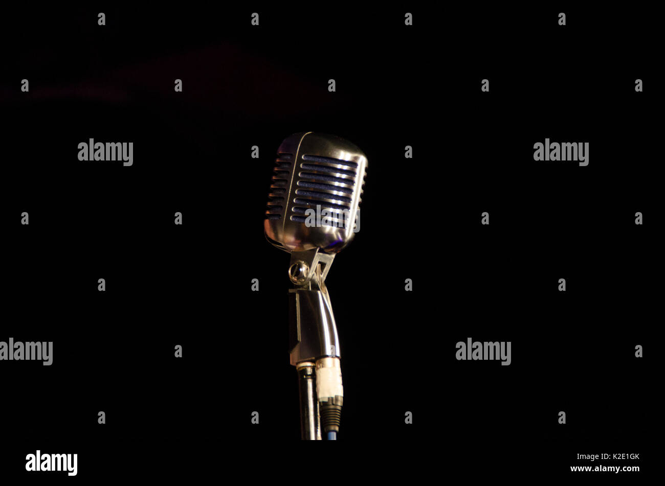 Old school vintage microphone with plain black background - Stock Image