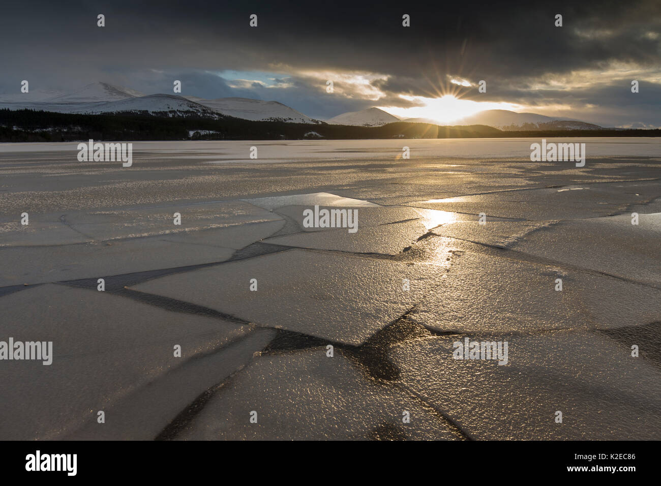 Frozen Loch Morlich at sunset with mountains in distance, Cairngorms National Park, Scotland, UK, January 2015. Stock Photo
