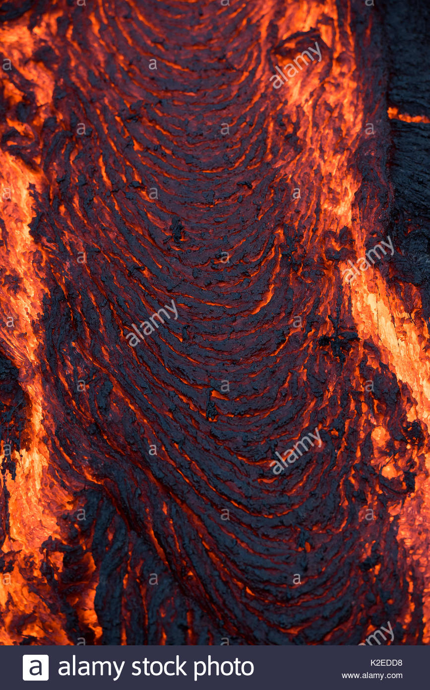 Pahoehoe lava from the 61G flow, emanating from Pu'u O'o on Kilauea Volcano, oozes from a breakout near the  Kamokuna ocean entry in Hawaii Volcanoes National Park, Kalapana, Puna, Hawaii, USA, July 2016 - Stock Image