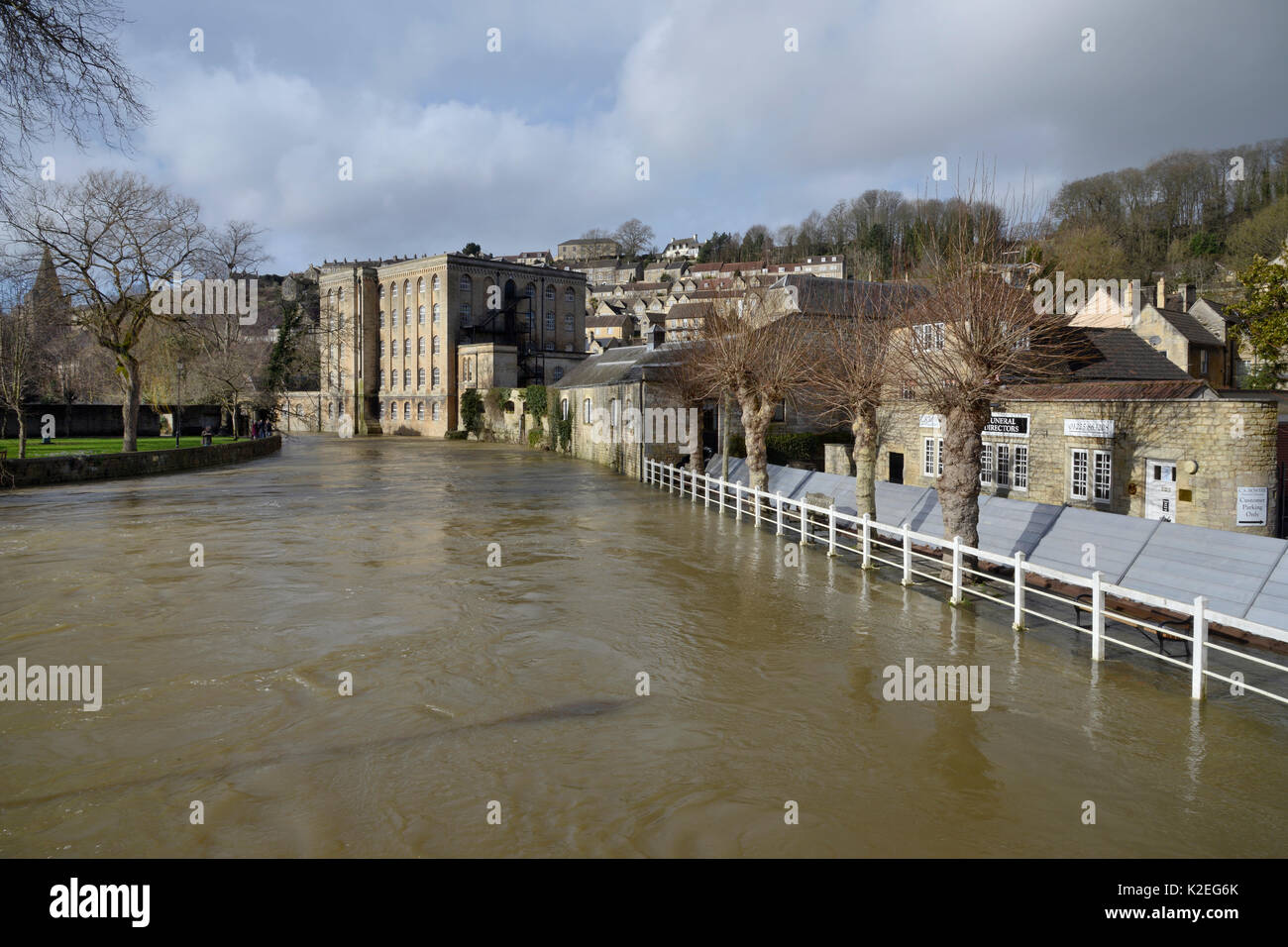 River Avon in spate through Bradford-on-Avon, with emergency flood defences to protect buildings from flooding, Stock Photo