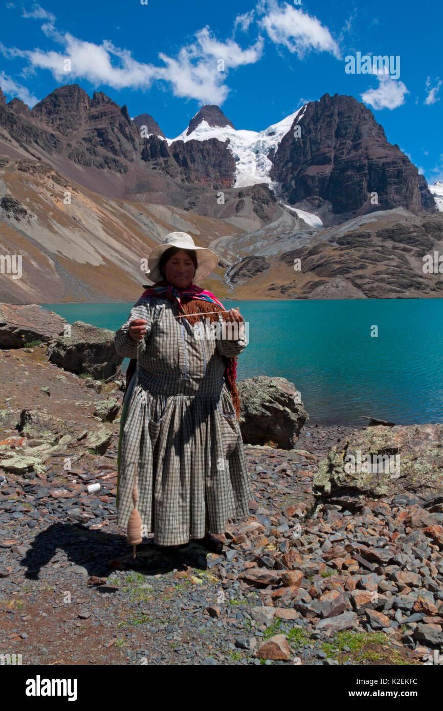 Bolivian woman spinning alpaca wool by hand. Ch'iyar Quta Lake, Bolivia. December 2016. - Stock Image