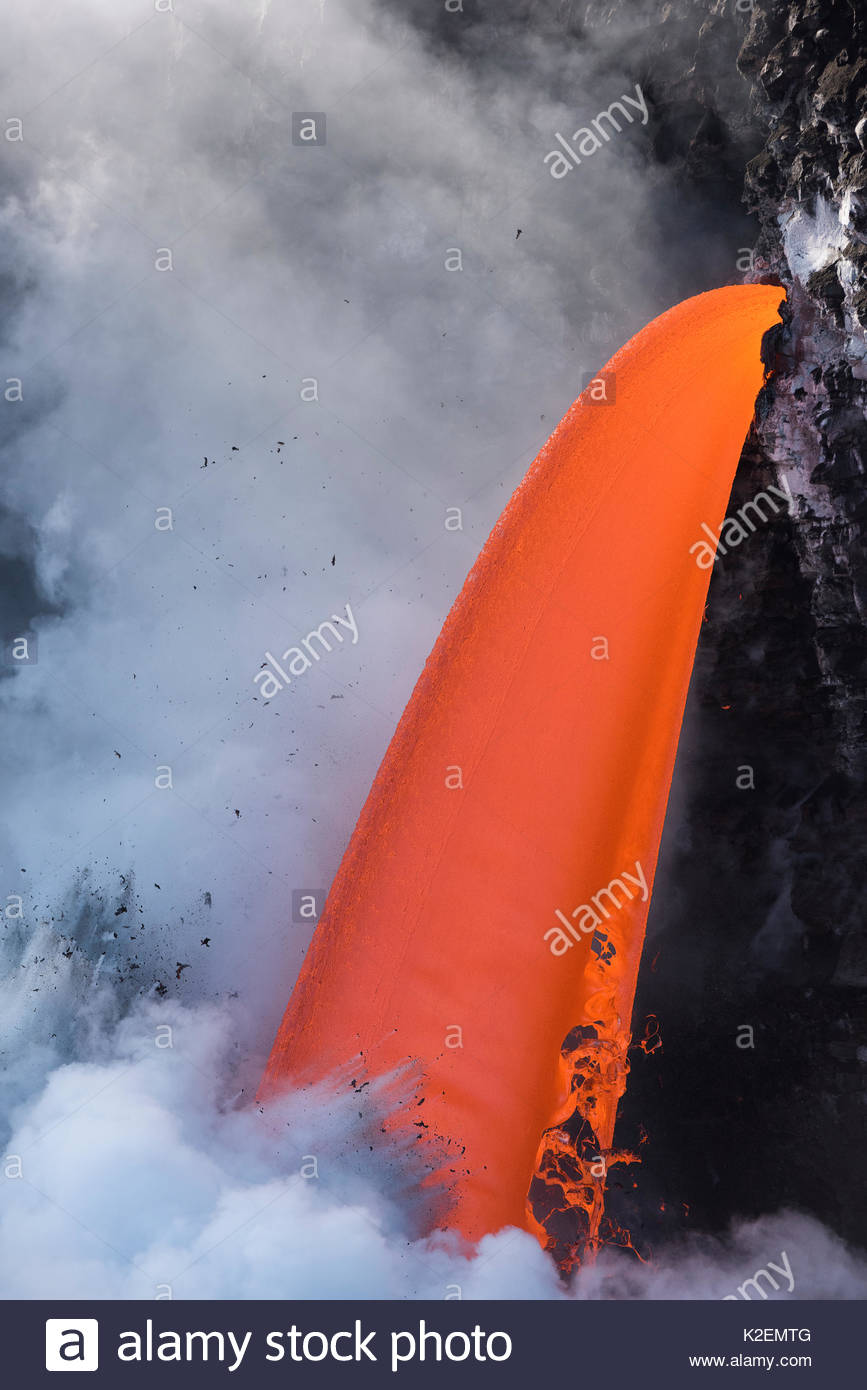 Hot lava from the 61G flow from Kilauea Volcano entering the Pacific Ocean from the open end of a lava tube at the Kamokuna entry in Hawaii Volcanoes National Park, producing steam explosions, Kalapana, Puna, Hawaii. January 2017. - Stock Image