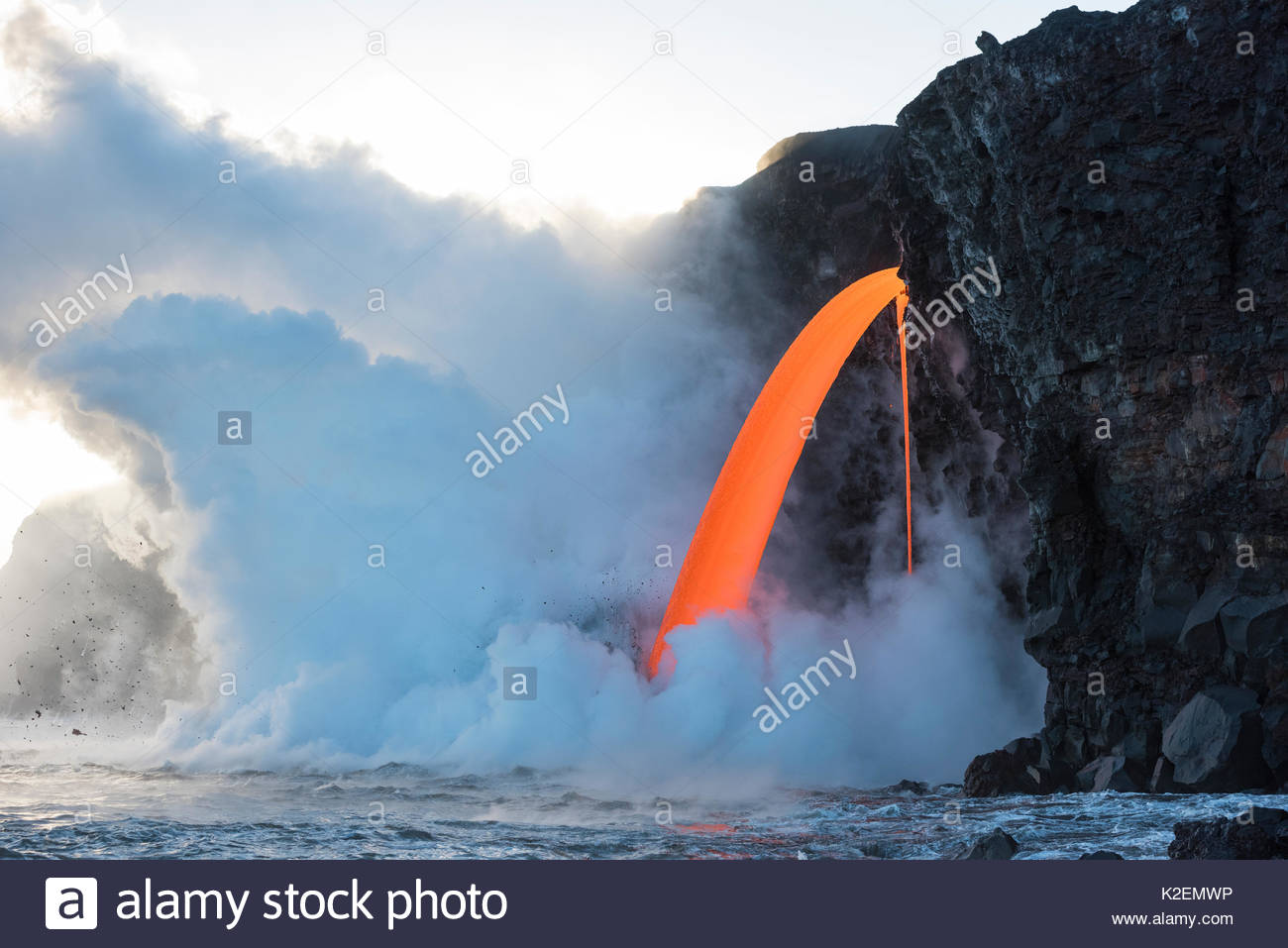 Hot lava from the 61G flow from Kilauea Volcano entering the ocean from the open end of a lava tube at the Kamokuna entry in Hawaii Volcanoes National Park, producing steam explosions, Kalapana, Puna, Hawaii. January 2017. - Stock Image