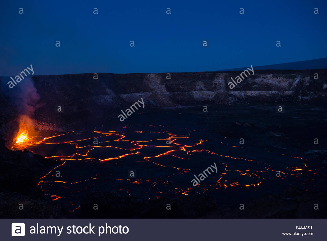 Hot lava fountains at a subduction zone at the edge of a lava lake, covered by plates of partially solidified cooled lava floating on its surface, in a pit within Halemaumau Crater, Kilauea Volcano, Hawaii. May 2015. - Stock Image