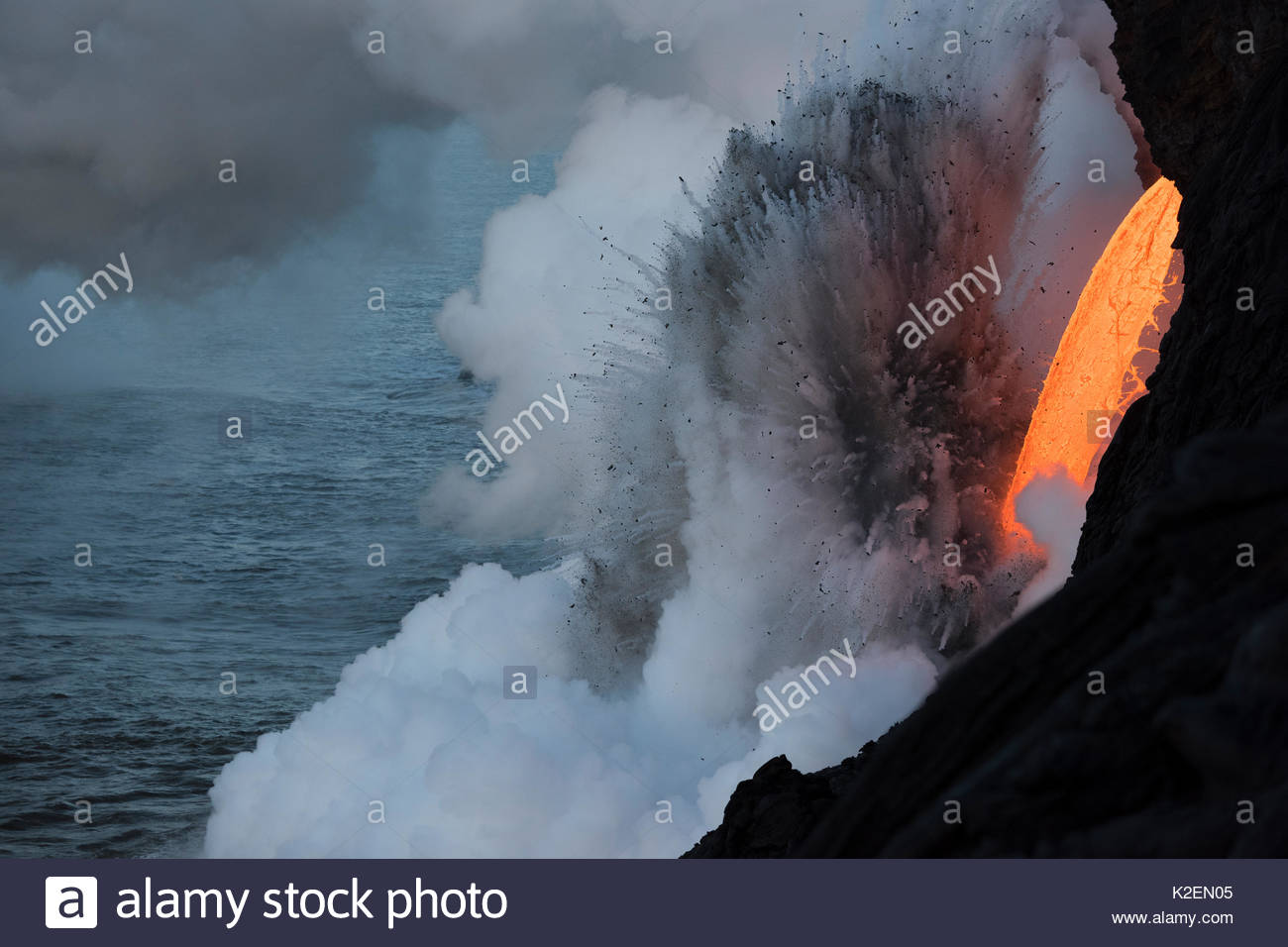 Hot lava from the 61G flow from Kilauea Volcano entering the ocean from the open end of a lava tube at the Kamokuna entry in Hawaii Volcanoes National Park, producing a great cloud of steam and violent explosions that throw hot pumice stones high into the air, Kalapana, Puna, Hawaii. January 2017. - Stock Image