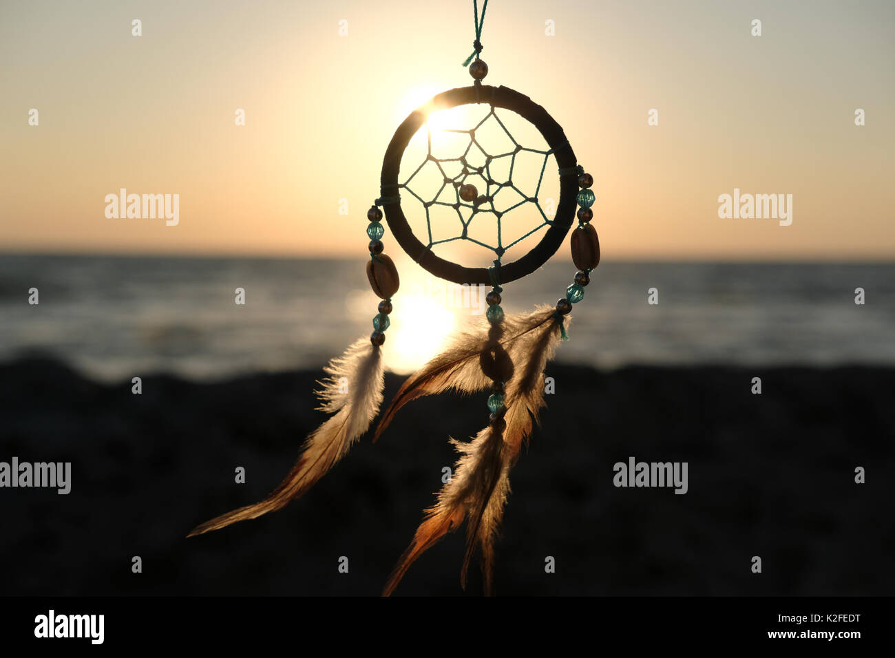 View on a sea sunset through a beautiful handmade dreamcatcher - Stock Image