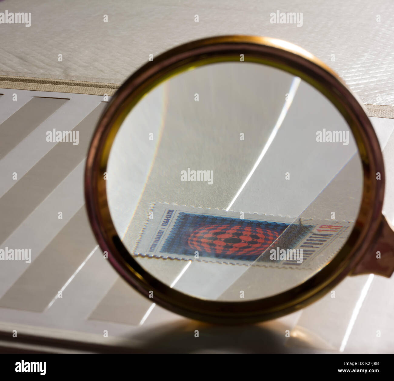 Look for the stamp in the white stamp-album through a magnifying glass. The concept of philately and collecting, selective focus - Stock Image