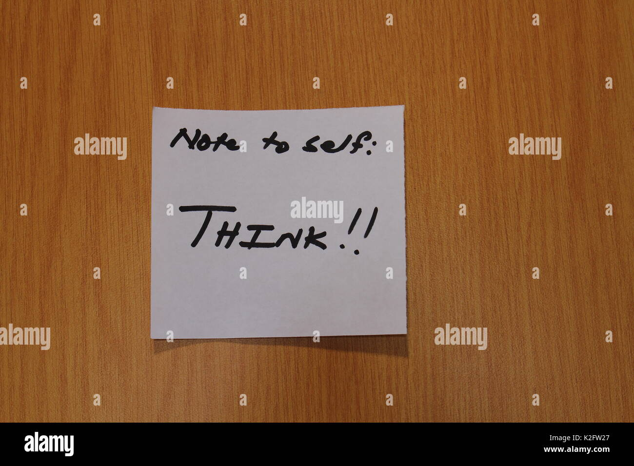 Hand written note with the term Think on it stuck to the wood surface of a notice board in landscape format a clear background and copy space - Stock Image