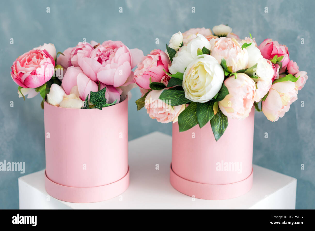 Flowers in round luxury present boxes. Bouquet of pink and white peonies in paper box. Mock-up of hat box of flowers with free copyspace for text. Interior decoration in in pastel colors. - Stock Image