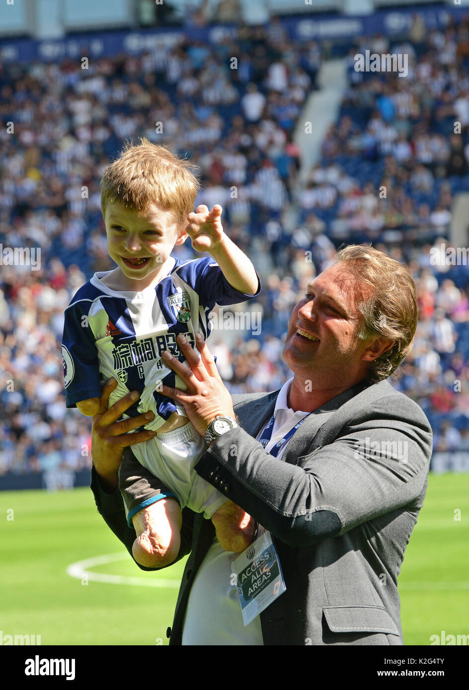 Young amputee Tommy Brown with former footballer Andy Johnson. Tommy had his limbs amputated after he contracted meningitis B aged 14 months. - Stock Image