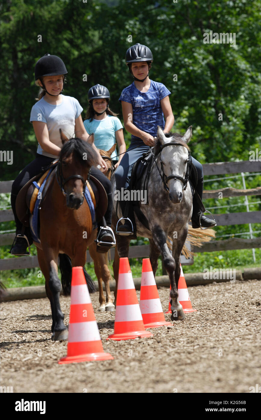 Group of young riders riding around traffic cones during a riding lesson. Switzerland - Stock Image