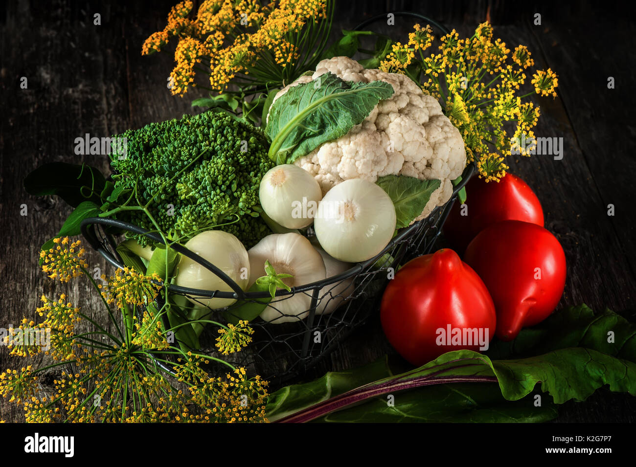 Mixed vegetables of cauliflower and broccoli, garlic, green onions, tomatoes and green peas on a wooden background in rustic style for Thanksgiving. - Stock Image