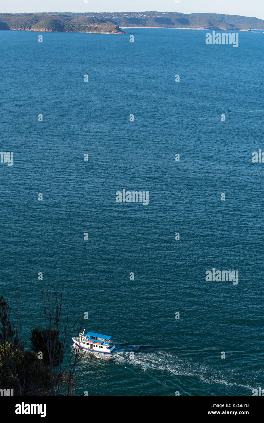 A small local ferry travels close to West Head on Sydney's Pittwater, Australia - Stock Image