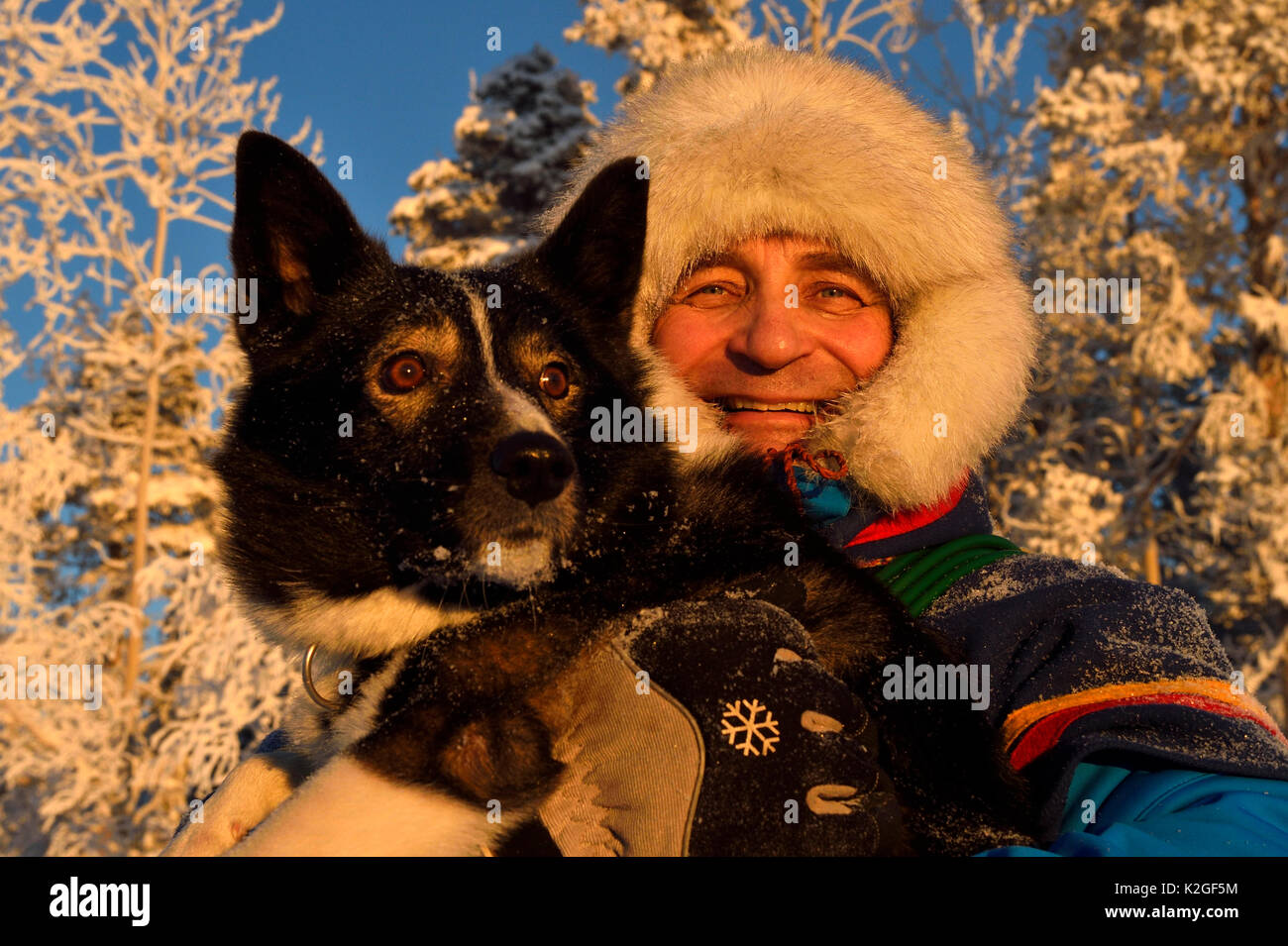 Nils-Torbjorn Nutti, owner and operator at Nutti Sami Siida, with domestic husky dog, during snowmobile trip into the wilderness, Jukkasjarvi, Lapland, Laponia, Norrbotten county, Sweden Model released. - Stock Image