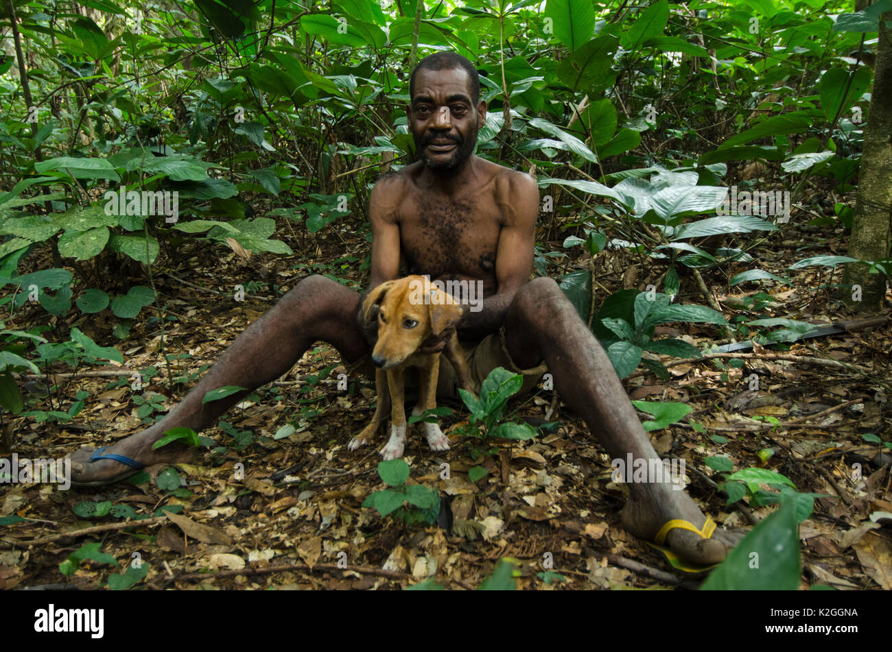 Ba'Kola Pygmy man in forest with dog. Mbomo, Odzala-Kokoua National Park, Republic of Congo (Congo-Brazzaville), Africa, June 2013. - Stock Image