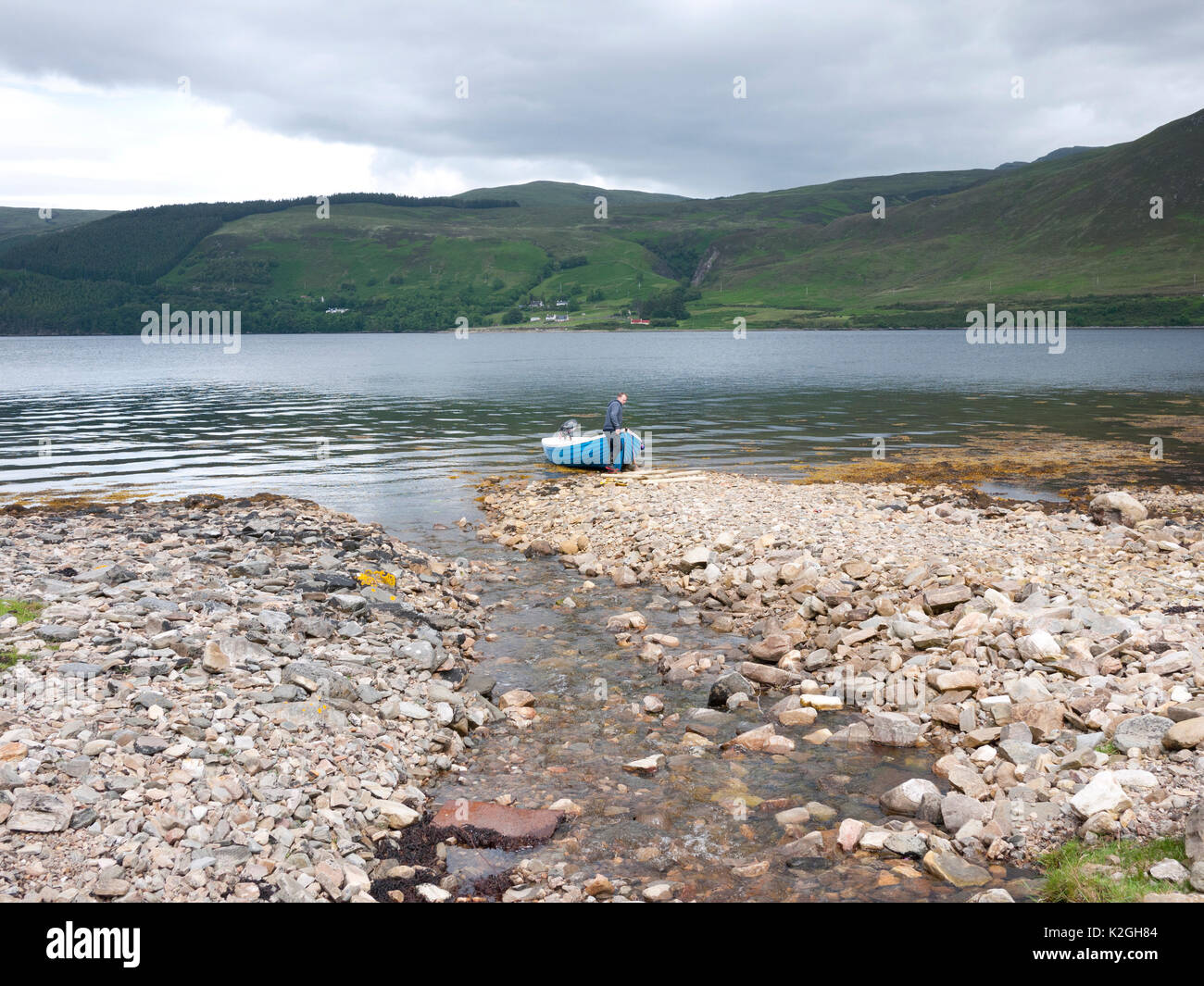 Young man hauling a boat out of Loch Broom, Scotland UK. - Stock Image
