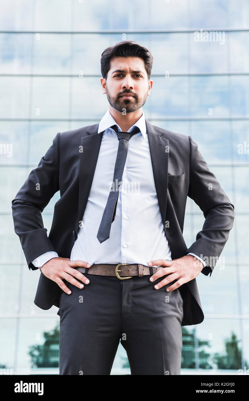 7bbd9cbb6f6 Arabic serious businessman or worker in black suit with tie and shirt with  beard standing in front of an office building on green grass in summer day.