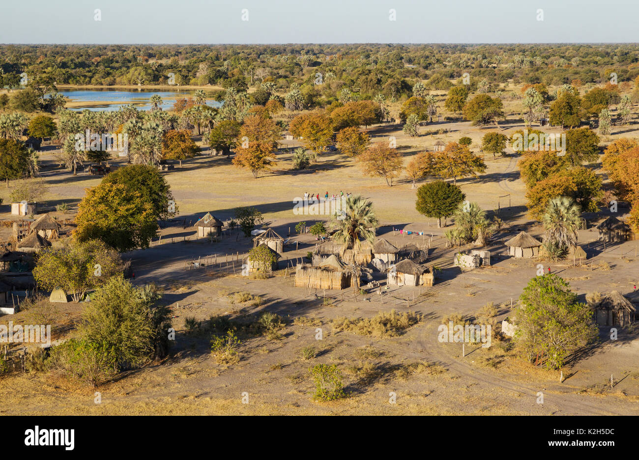 Native village just outside of the protected area, prominent a group of young men getting ready for a football match, aerial view, Okavango Delta, Botswana - Stock Image