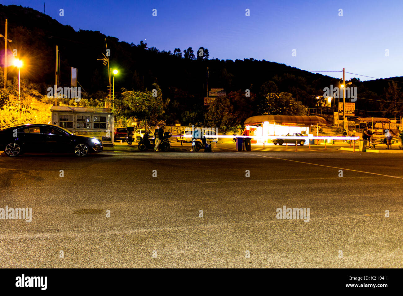 Cars waiting in line at the port of Agia Marina, Marathonas, Greece to embark on the ferry boat to Nea Styra, Euboia. - Stock Image