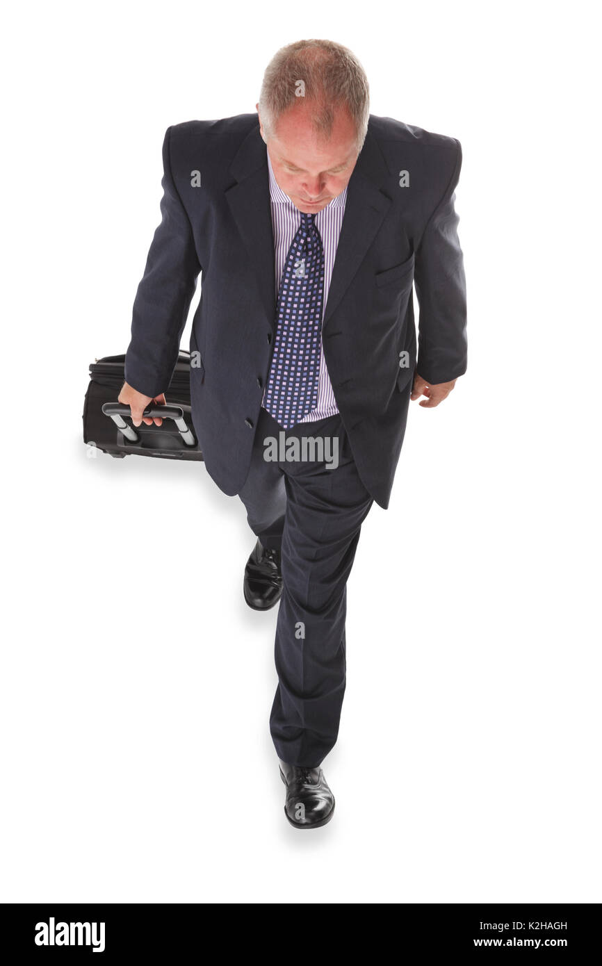 Overhead photo of a businessman in a suit pulling a travelling suitcase, isolated on a white background. - Stock Image