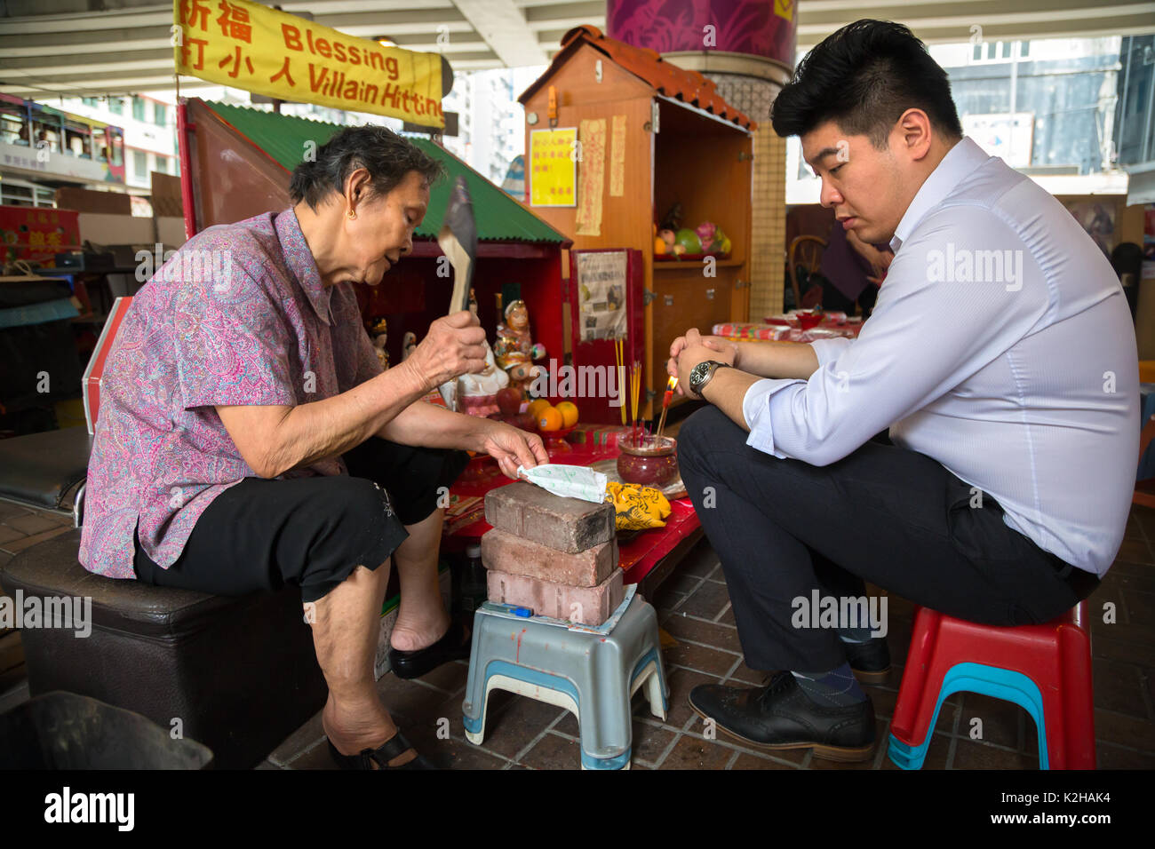 Hong Kong lady doing the  'vilain hitting' sorcery practice - local beliefs - Stock Image
