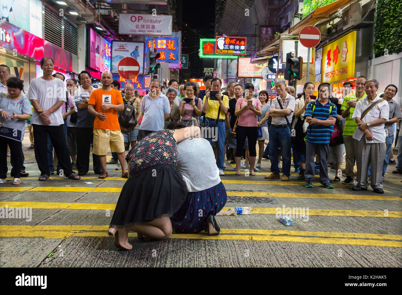 Crowd during live performance in the streets of Mong Kok on a Saturday night. - Stock Image