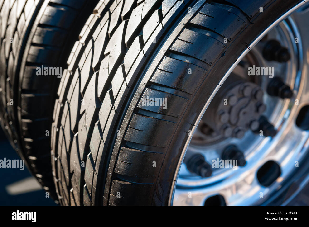 Closeup view of a dual tire wheel of a modern sports car. Black rubber dual tire and metal alloy web of the wheel. - Stock Image