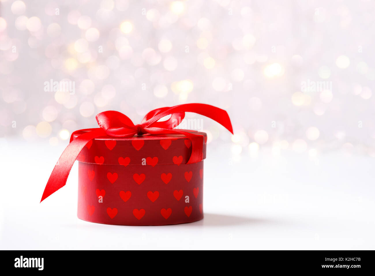 Holiday background, red gift box with hearts and ribbon over festive ...