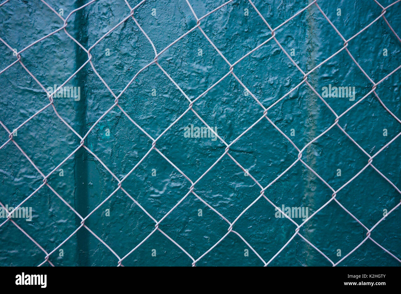 wire fence over green metallic background - Stock Image