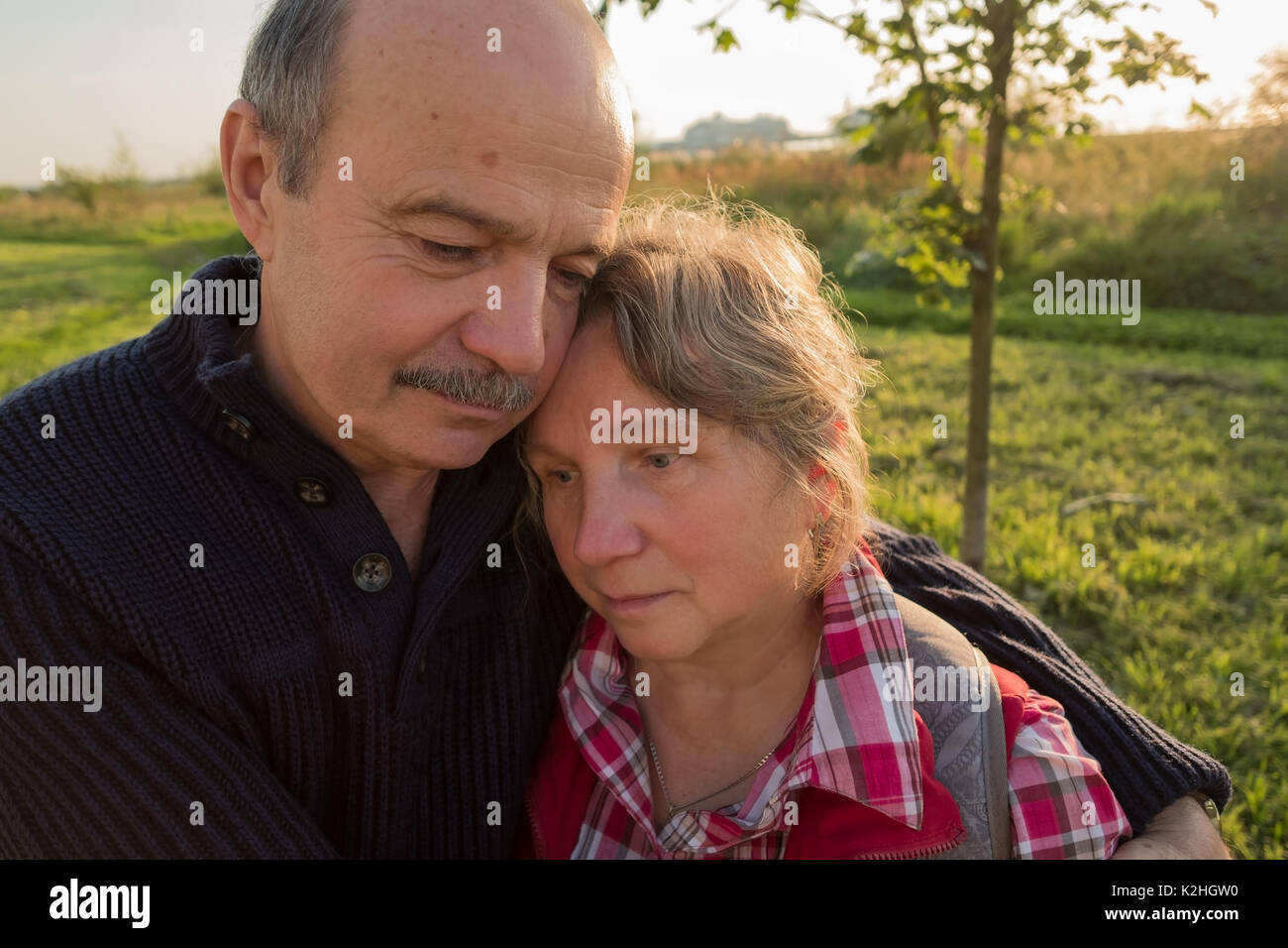 Sad elderly couple. Coping with problems together. - Stock Image