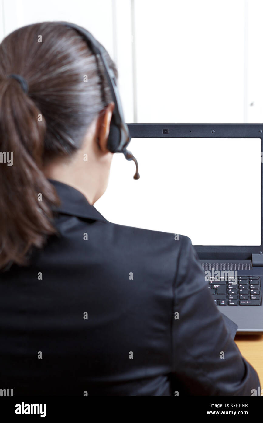 Rear view of a woman in a black blazer with headset and microphone in front of her computer, white, empty screen, Stock Photo
