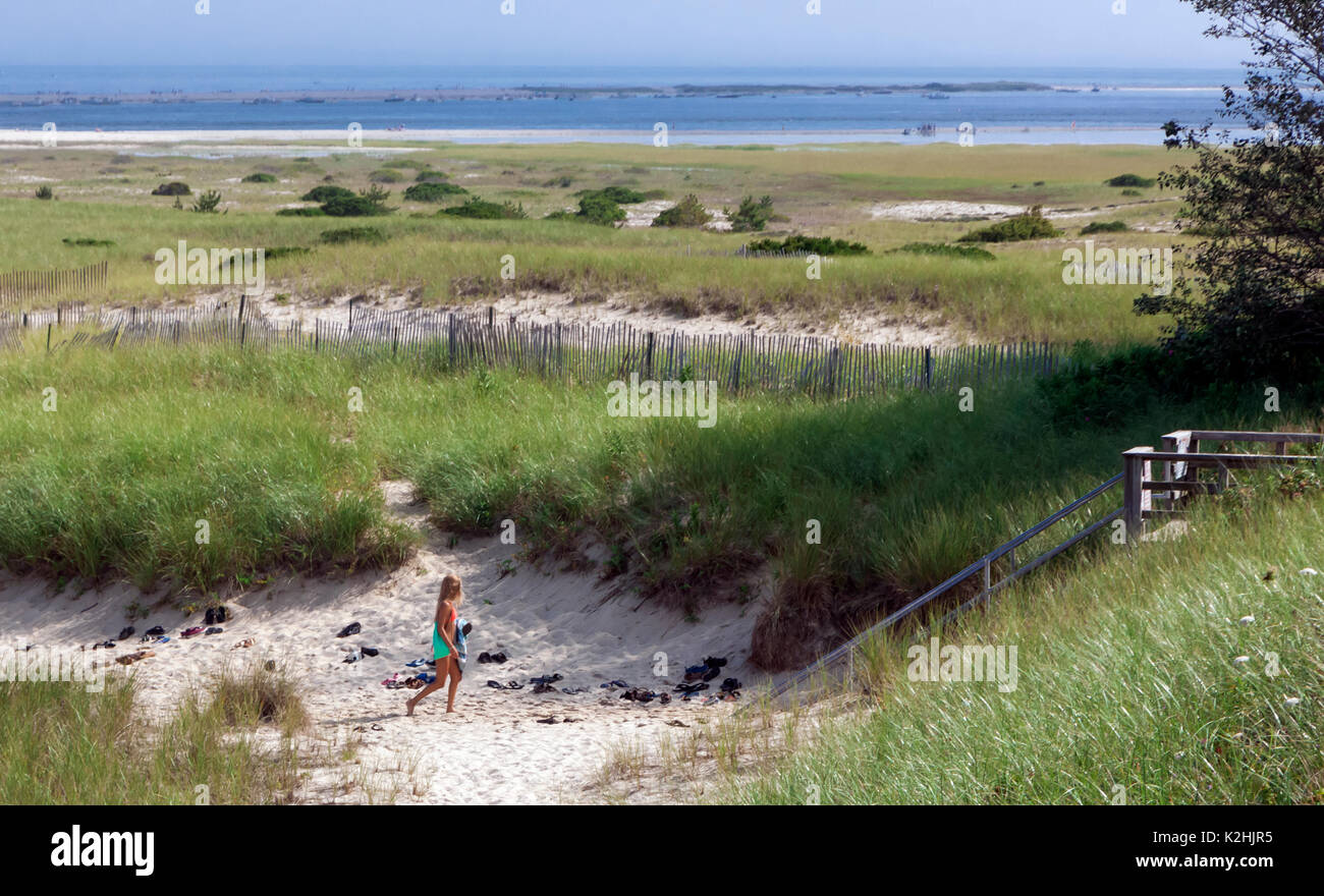 Teenage female leaving the beach after a day of sunbathing. - Stock Image