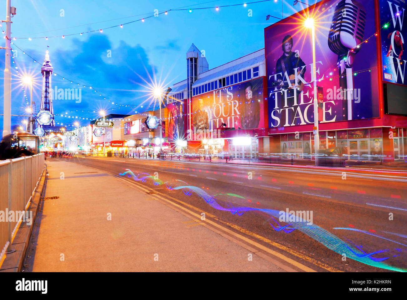 Light trails from bicycles riding along Blackpool Promenade in front of Madame Tussaud's waxworks during the annual Stock Photo