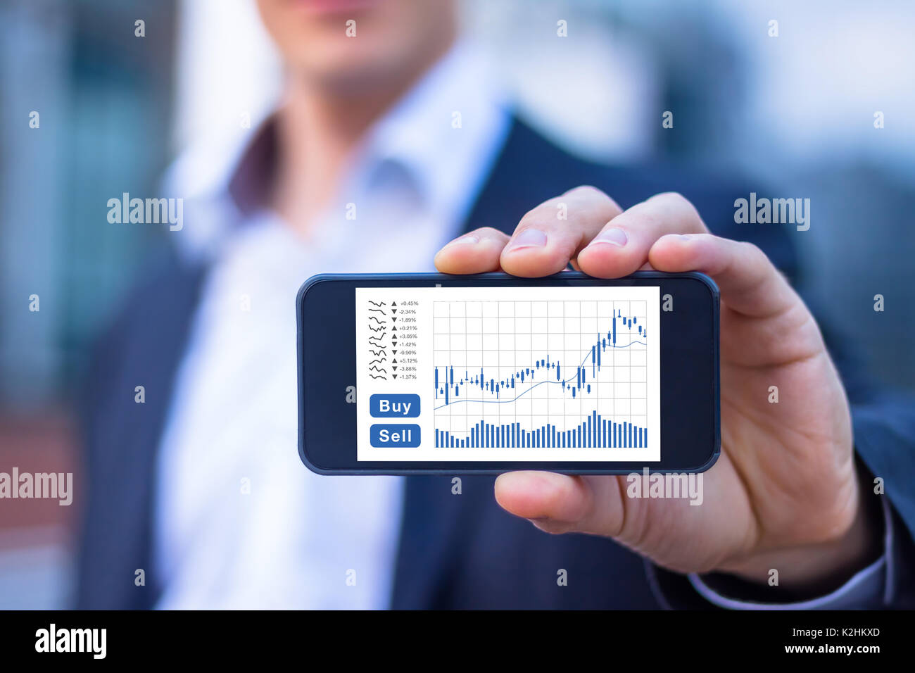Trader showing smartphone screen with trading interface dashboard with candlestick chart, quotes and buy sell buttons, stock exchange and fintech conc - Stock Image