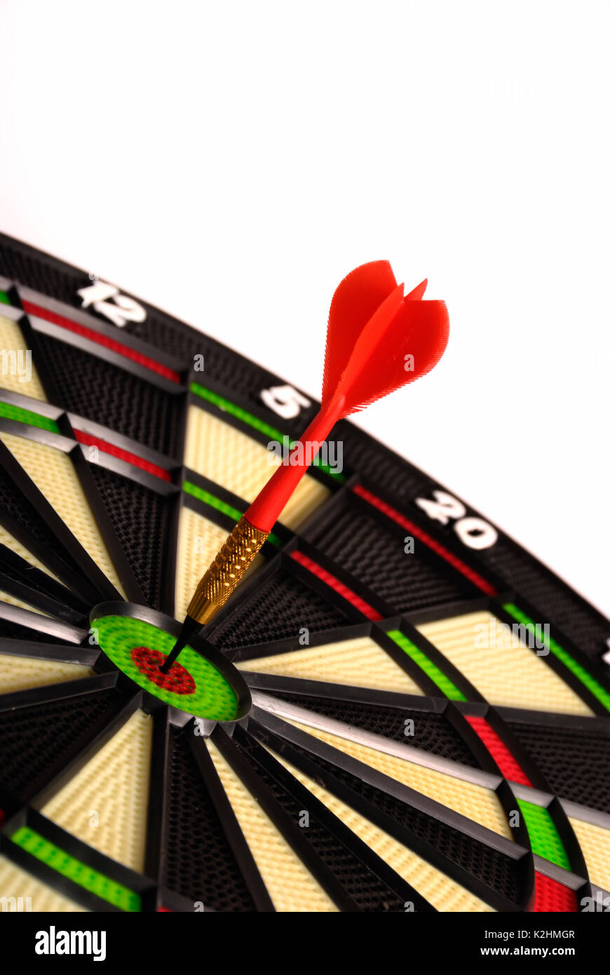 red dart hitting the bull's eye on a target - Stock Image