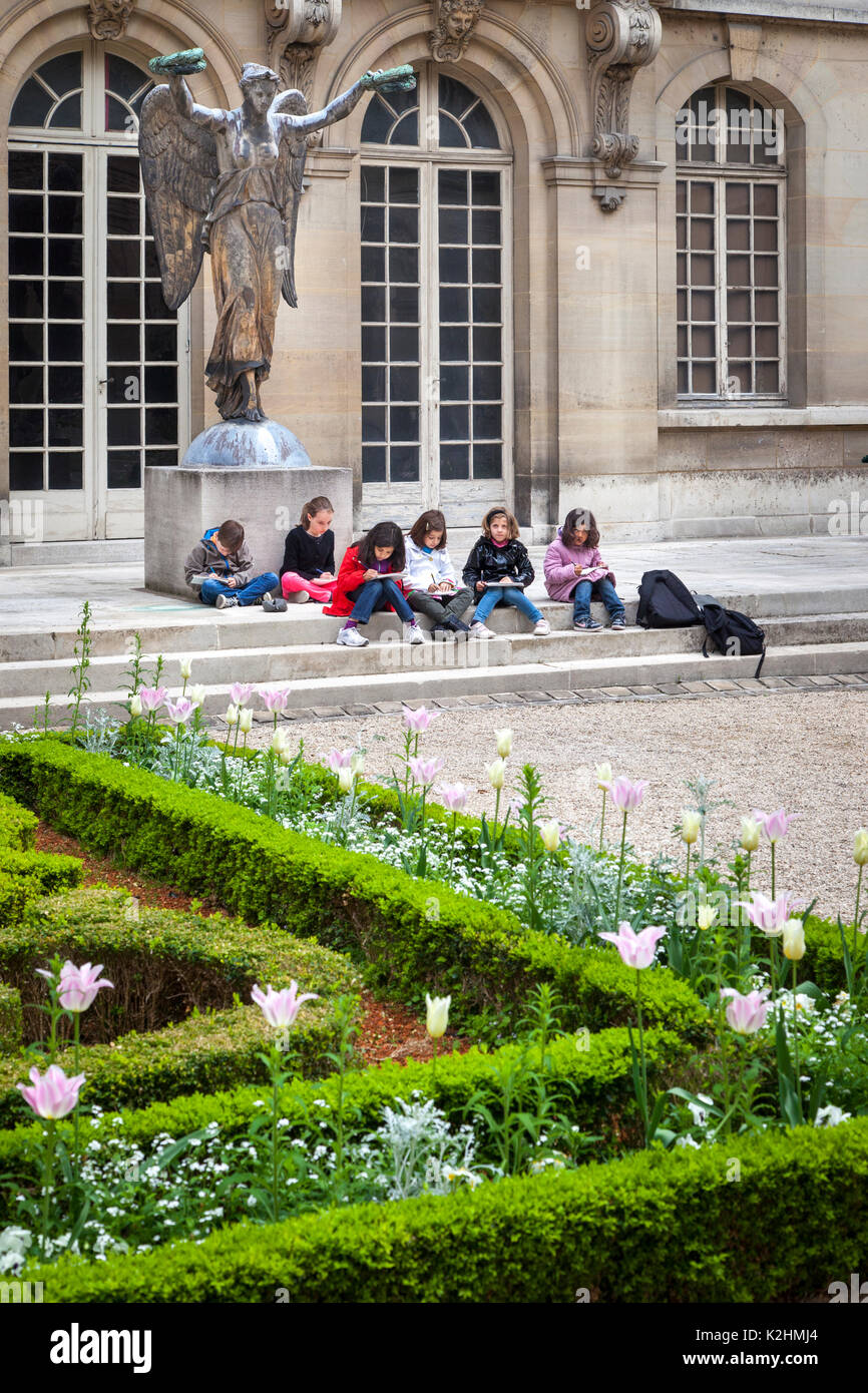 Young art students creating drawings at Hotel Carnavalet in the Marais, Paris France - Stock Image
