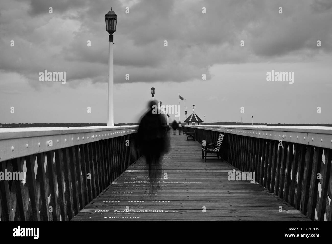 A mystery figure on the all wooden pier of Yarmouth based on the Isle Of Wight - Stock Image