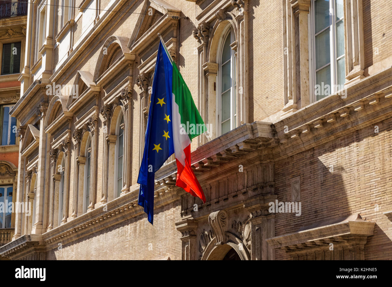 Italian and European Union flags on facade of the building in Rome, Italy - Stock Image