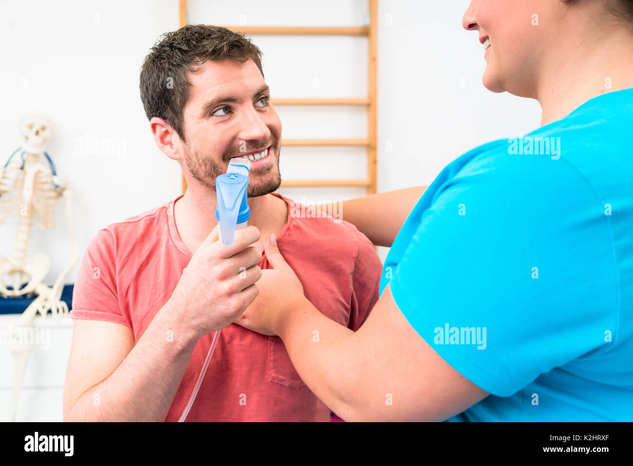 Man taking pulmonary function test with mouthpiece in his hand - Stock Image