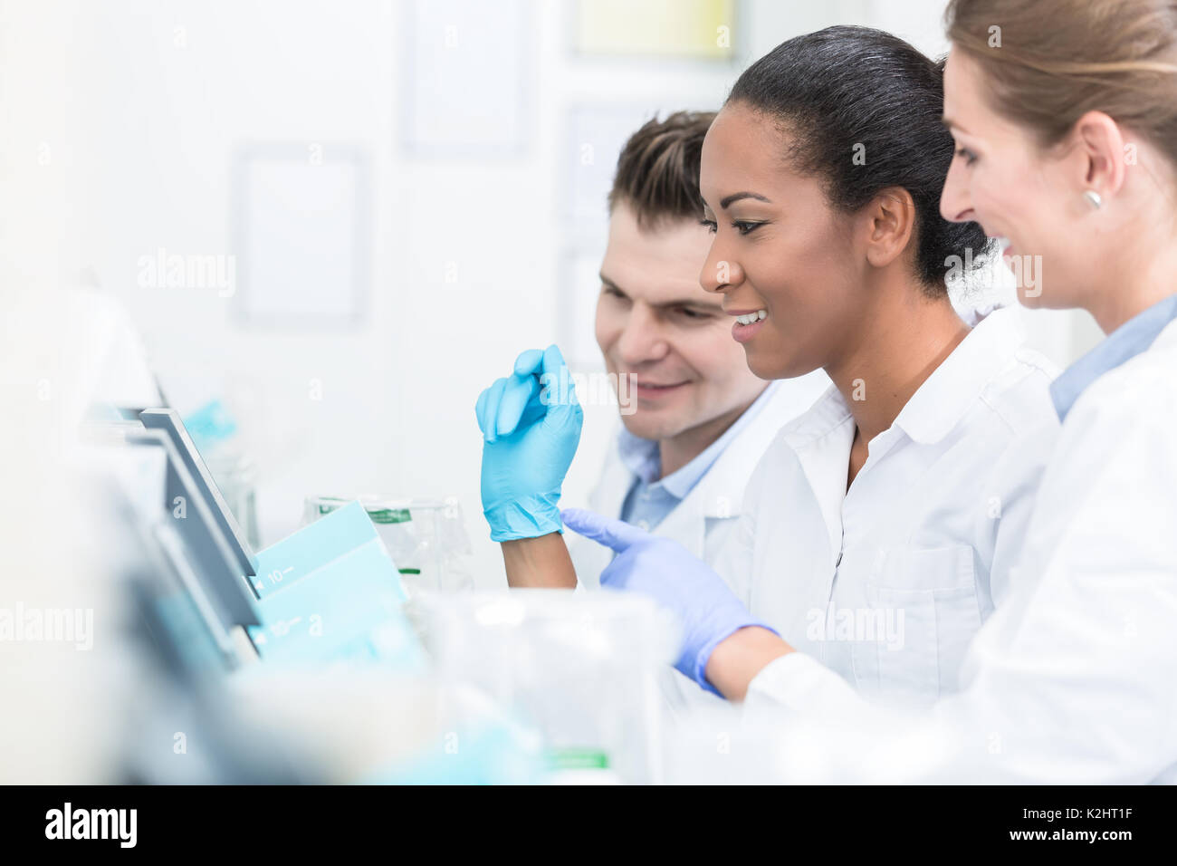 Group of researchers during work on devices in laboratory - Stock Image