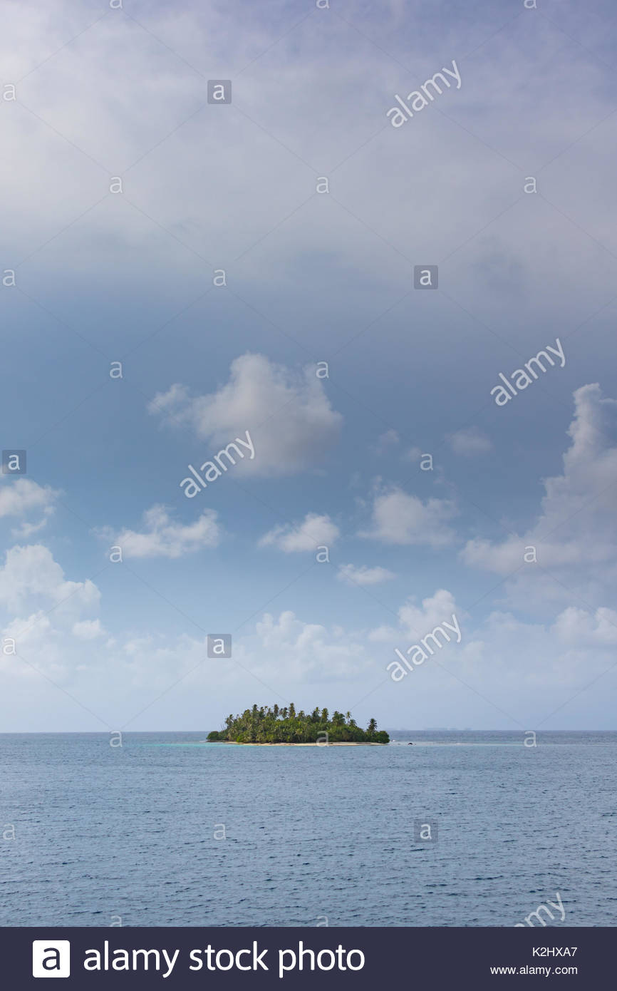 A lone tropical island sits in the Caribbean Sea under a partly cloudy sky - Stock Image