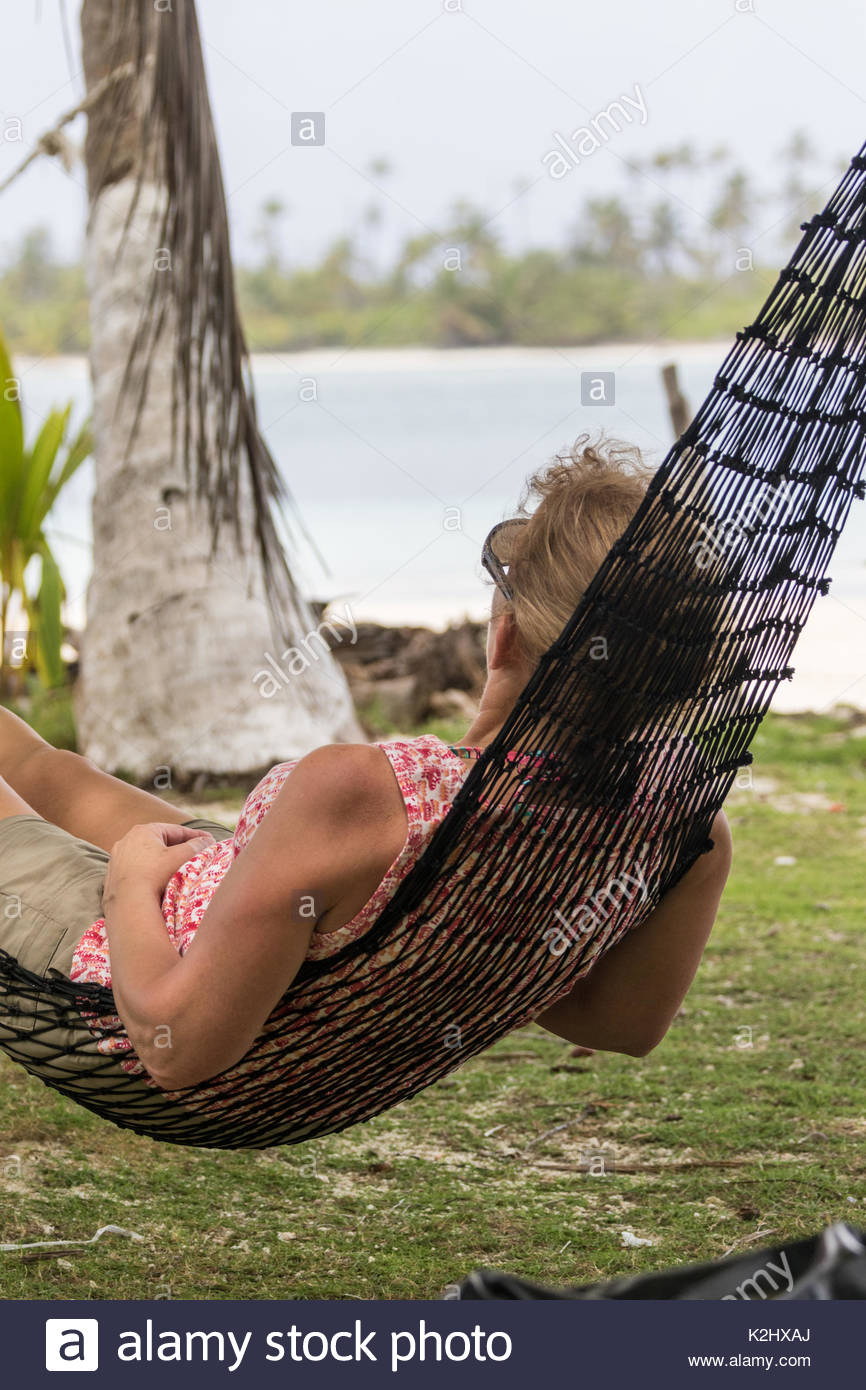 A woman relaxes in a tropical hammock strung between two coconut trees while lazily gazing at the white sand beaches of the Caribbean Sea in Panama. - Stock Image